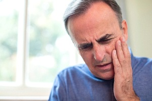 Man in blue shirt who is experiencing tooth pain