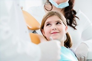 Young girl in dental exam chair looking at dentist