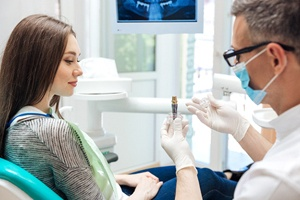 A dentist holds up a model of a dental implant while explaining to a female patient how it works