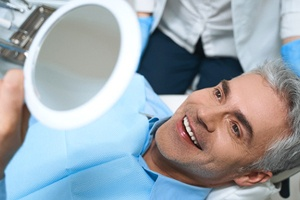 A middle-aged man admiring his new smile in the mirror after receiving dental implants