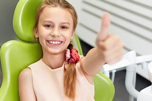 Young girl in dental chair giving thumbs up