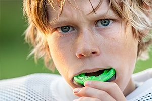 Teen boy placing sports mouthguard
