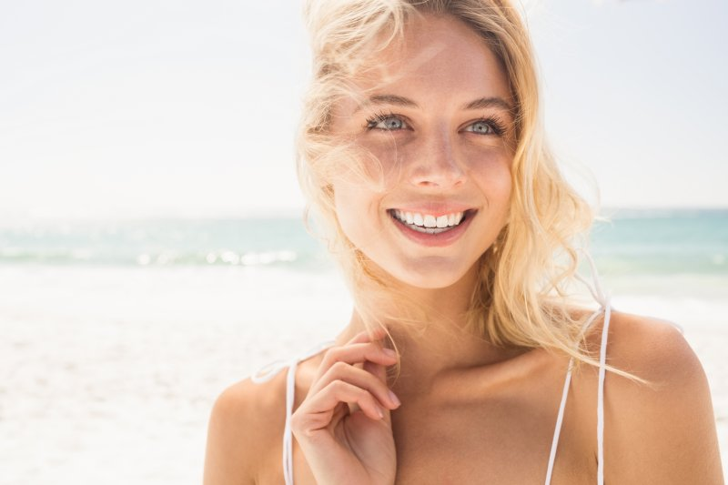 A woman smiling at the beach.