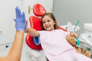 Young girl high-fives Lake Dallas sedation dentist