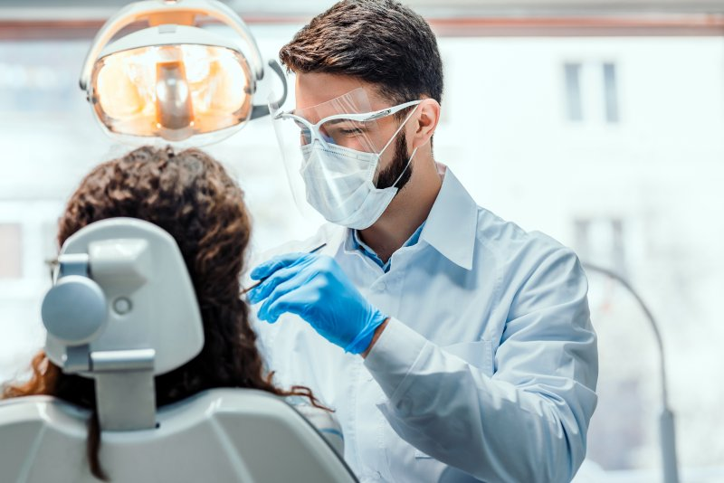 a male emergency dentist in Lake Dallas wearing PPE while caring for a patient