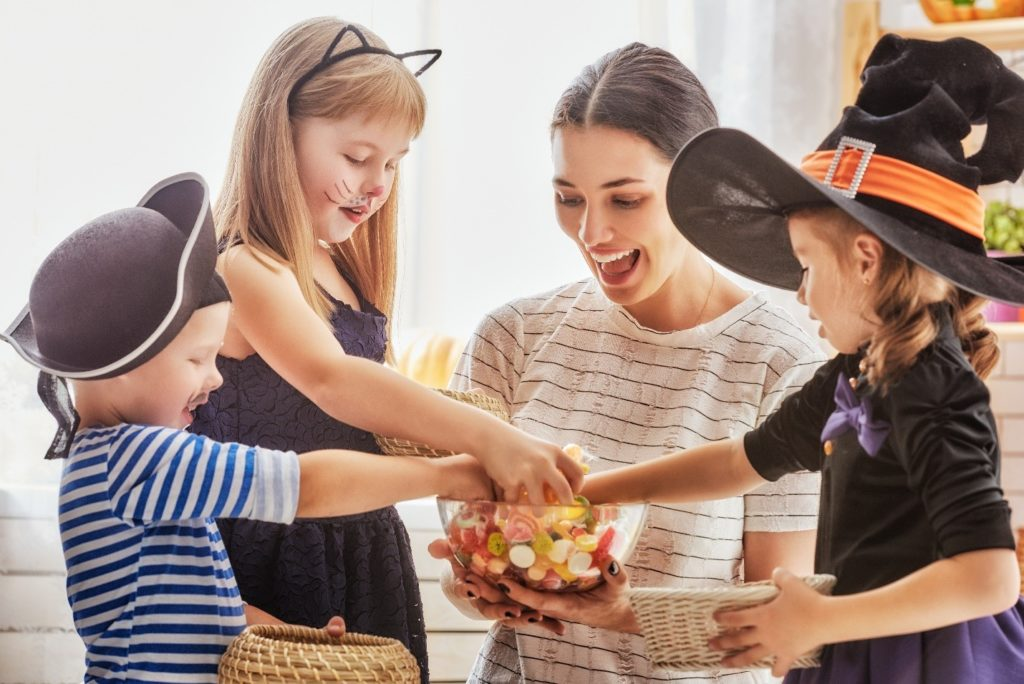 Mom sharing Halloween candy with kids in costumes
