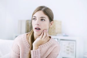 Woman with jaw pain, considering dental implants in Lakewood, Dallas