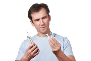 man looking at toothbrushes
